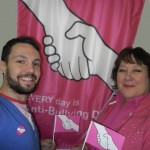 The Flag Shop Saskatoon celebrates Pink Shirt Day in front of their banner.